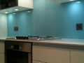 Blue back painted toughen splashback in northern ireland with glass cut outs for plugs.png